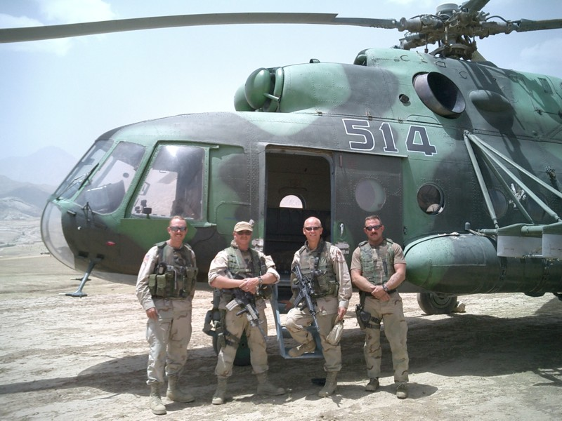 Four soldiers standing by a helicopter